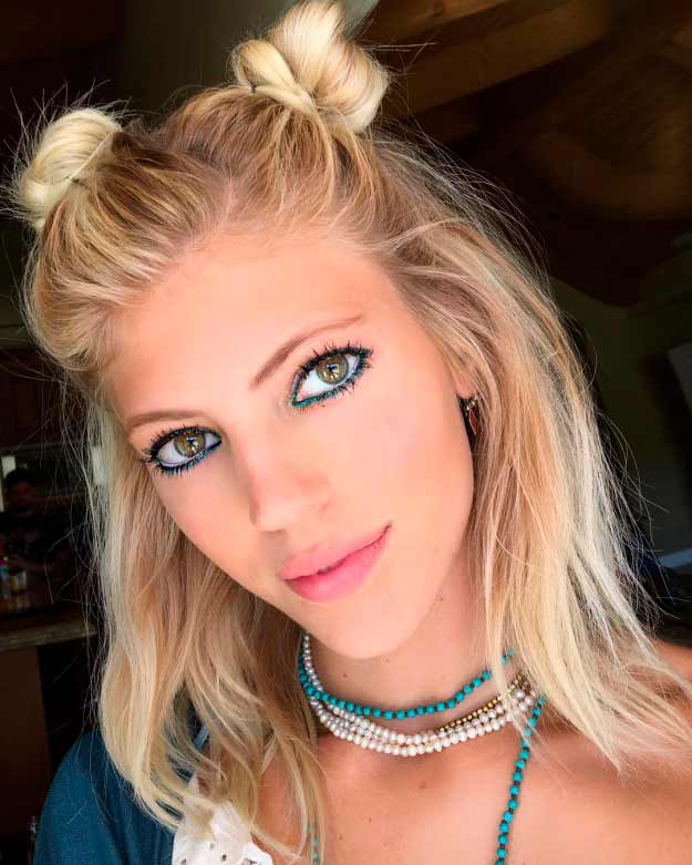 Peinado de la modelo Devon Windsor con dos moños sobre pelo corto