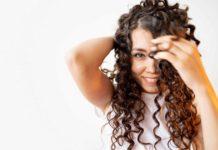 Mujer luce cabello rizado con el método curly girl